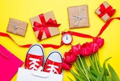 Bündel rote Tulpen, rote Gummiüberschuhe, kühle Einkaufstaschen, Band, a Stockfotos