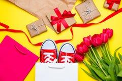 Bündel rote Tulpen, rote Gummiüberschuhe, kühle Einkaufstaschen, Sachen FO Stockbilder