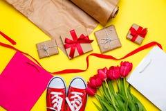Bündel rote Tulpen, rote Gummiüberschuhe, kühle Einkaufstaschen, Sachen FO Stockfoto