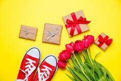 Bündel rote Tulpen, rote Gummiüberschuhe und schöne Geschenke auf gewonnen Lizenzfreie Stockbilder