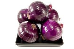 Bündel rote Zwiebeln auf einer schwarzen Platte lizenzfreies stockbild