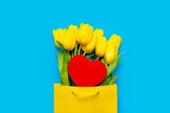 Bündel schöne gelbe Tulpen in der kühlen Einkaufstasche und im Herzen Stockbilder