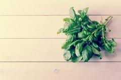 Bündel Spinat auf einem weißen hölzernen backgroun Lizenzfreie Stockfotografie