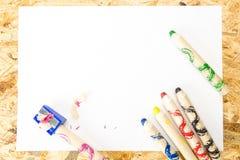 Bündel starke bunte Bleistifte für Kinder und Bleistiftspitzer mit Schnitzeln Lizenzfreie Stockfotografie