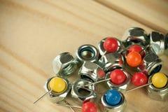 Bündel vereinbarte Stifte mit klaren bunten Nadelköpfen und industriellen Metallnüssen schraubt Stockbilder