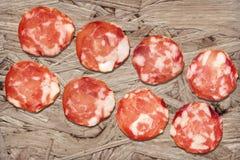 Bündel von acht Schweinefleisch-Salami-Scheiben eingestellt auf rustikale hölzerne Spanplatten-raue Schmutz-Oberfläche Stockfoto