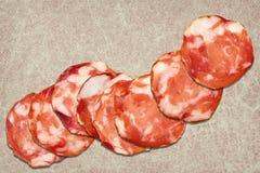 Bündel von acht Schweinefleisch-Salami-Scheiben eingestellt auf rustikalen Weinlese-Pergament-Platz Mat Grunge Surface Lizenzfreies Stockfoto
