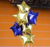 Bündel von blauer und gelber Plastik steigt mit orange Wand im Ballon auf stockfotografie