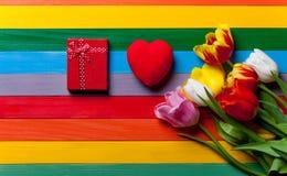 Bündel von den Tulpen, von rotem Herzen und von Geschenk, die auf dem Tisch liegt Stockfotos