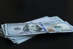 Bündel von 100 Dollarscheinen auf schwarzem Hintergrund Stockfoto