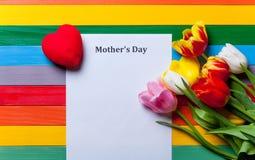 Bündel von Tulpen, von Herzen und von Blatt des Papiers, das auf dem Tisch liegt Lizenzfreie Stockfotos