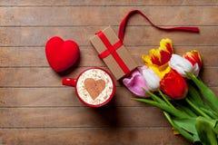 Bündel von Tulpen, von Herzen, von Geschenk und von Tasse Kaffee, der auf dem ta liegt Lizenzfreies Stockfoto