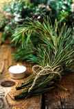 Bündel von Weihnachtstannenbaum- oder -kiefernniederlassungen und von glühender Kerze Stockfotografie