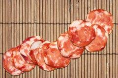 Bündel von zehn Schweinefleisch-Salami-Scheiben eingestellt auf rustikale Weinlese-Bambusplatz Mat Grunge Surface Lizenzfreies Stockbild