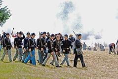 Bürgerkrieg reenactors, die über ein Schlachtfeld marschieren Lizenzfreie Stockbilder