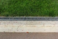 Bürgersteigseiten- und Regenwasserableitung in einem Park Stockfotos
