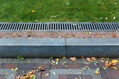 Bürgersteigseiten- und Regenwasserableitung in einem Park Stockbilder