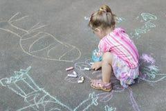 Bürgersteigskreidezeichnungen des kleinen kaukasischen Mädchens, das rosa Rüschenrock trägt Lizenzfreie Stockbilder