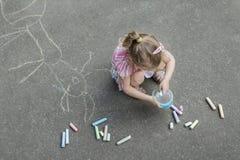Bürgersteigsweissen des kleinen blonden Mädchens, das rosa Rüschenrock trägt Stockbild