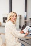 Büro-Frau, die an ihrem Schreibtisch hält ein Buch sitzt stockfotografie