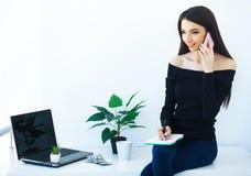 Büro-Geschäftsfrau, die auf dem Tisch lächelt und sitzt Frauen-Dr. lizenzfreie stockfotos