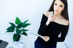 Büro-Geschäftsfrau, die auf dem Tisch lächelt und sitzt Frauen-Dr. lizenzfreie stockfotografie