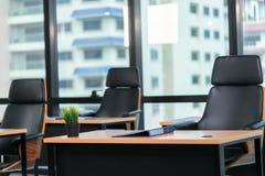 Büro mit hölzernem Schreibtisch und schwarzer Eexcutive-Stuhl mit Geschäftsstadthintergrund stockfotografie