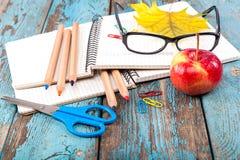 Büro oder Schulbedarf auf den hölzernen Planken gemalt im Blau Lizenzfreie Stockfotos