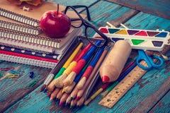 Büro oder Schulbedarf auf den hölzernen Planken gemalt im Blau Lizenzfreies Stockfoto