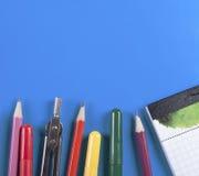 Büro und Schulbedarf auf einem blauen Hintergrund Lizenzfreies Stockbild