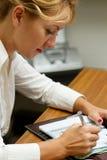 Büroangestellt-Frauenschreiben im Tagebuch Stockfoto