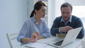 Büroangestellte, die über Projekt am Laptop zusammenarbeiten stock video