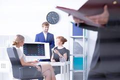 Büroangestellte, die bei der Arbeit sitzen stockfoto