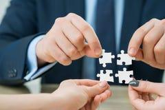 Büroangestellte, die Puzzlespiele halten Stockfotos
