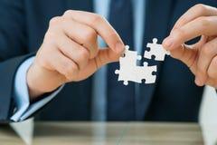 Büroangestellte, die Puzzlespiele halten Lizenzfreies Stockbild