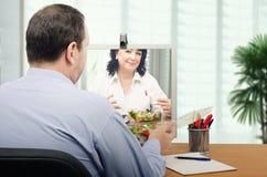 Büroangestellte, die zusammen online essen Lizenzfreie Stockfotos