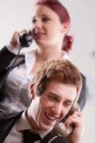 Büroangestellte in einem Call-Center mit Telefonen Stockbild