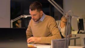 Büroangestellte mit dem Laptop, der nachts arbeitet stock footage