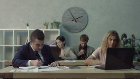 Büroangestellten, die Routinearbeit im Büro erledigen stock footage