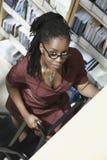 Büroangestellter auf Leiter im Aktenspeicherungs-Raum Lizenzfreie Stockfotografie
