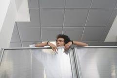 Büroangestellter, der über Zellen-Wand blickt Stockfotos