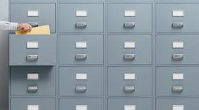 Büroangestellter, der eine Datei von einem Aktenschrank nimmt Stockfoto