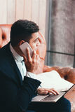 Büroangestellter, der Laptop und Mobiltelefon verwendet Lizenzfreie Stockfotografie