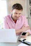 Büroangestellter, der Laptop und Telefon verwendet lizenzfreies stockbild