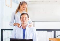 Büroangestellter, der Massage auf seinem Arbeitsplatz erhält stockbild