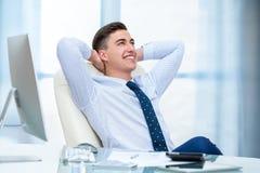 Büroangestellter, der am Schreibtisch träumt Stockbilder