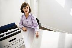 Büroangestellter, der am Tisch mit Kasten Dateien sitzt lizenzfreie stockbilder