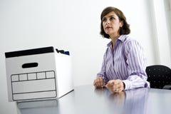 Büroangestellter, der am Tisch mit Kasten Dateien sitzt stockbilder