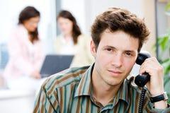 Büroangestellter, der um Telefon ersucht Stockbilder