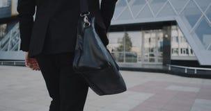 Büroangestellter kommt zum modernen Geschäftszentrum herein, das seinen Aktenkoffer hält stock video
